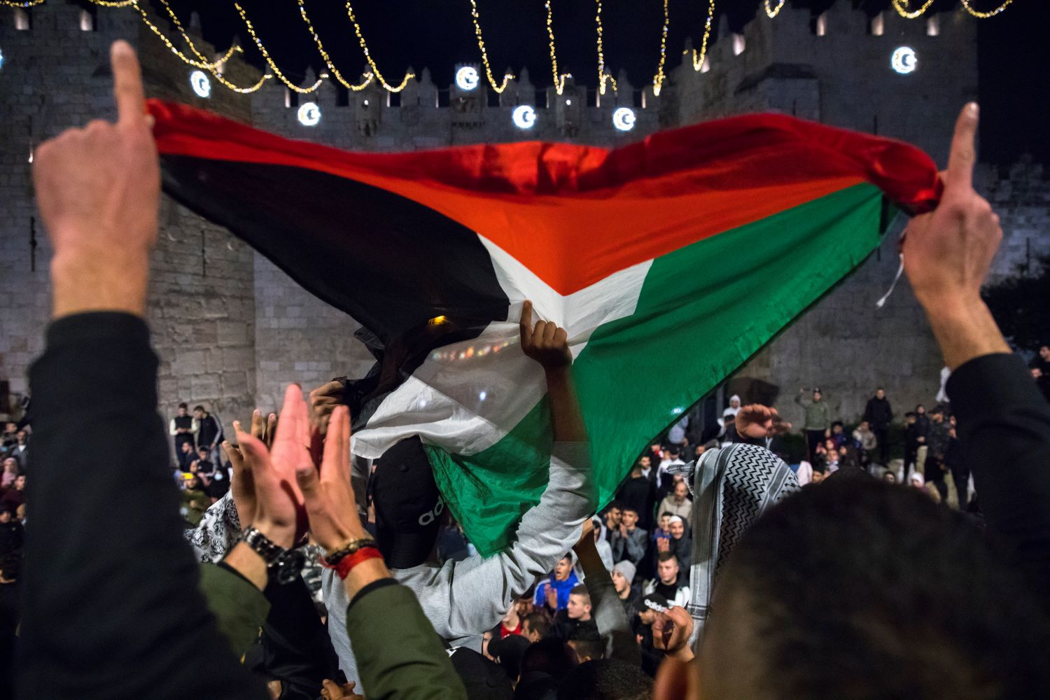 Palestinians gather and wave flags at Damascus Gate in Jerusalem's Old City, during the holy Muslim month of Ramadan, April 26, 2021. (Olivier Fitoussi/Flash90)