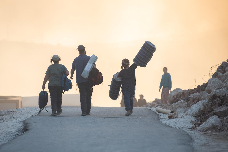 Israeli settlers seen walking through the settlement outpost of Eviatar, West Bank, June 21, 2021. (Sraya Diamant/Flash90)