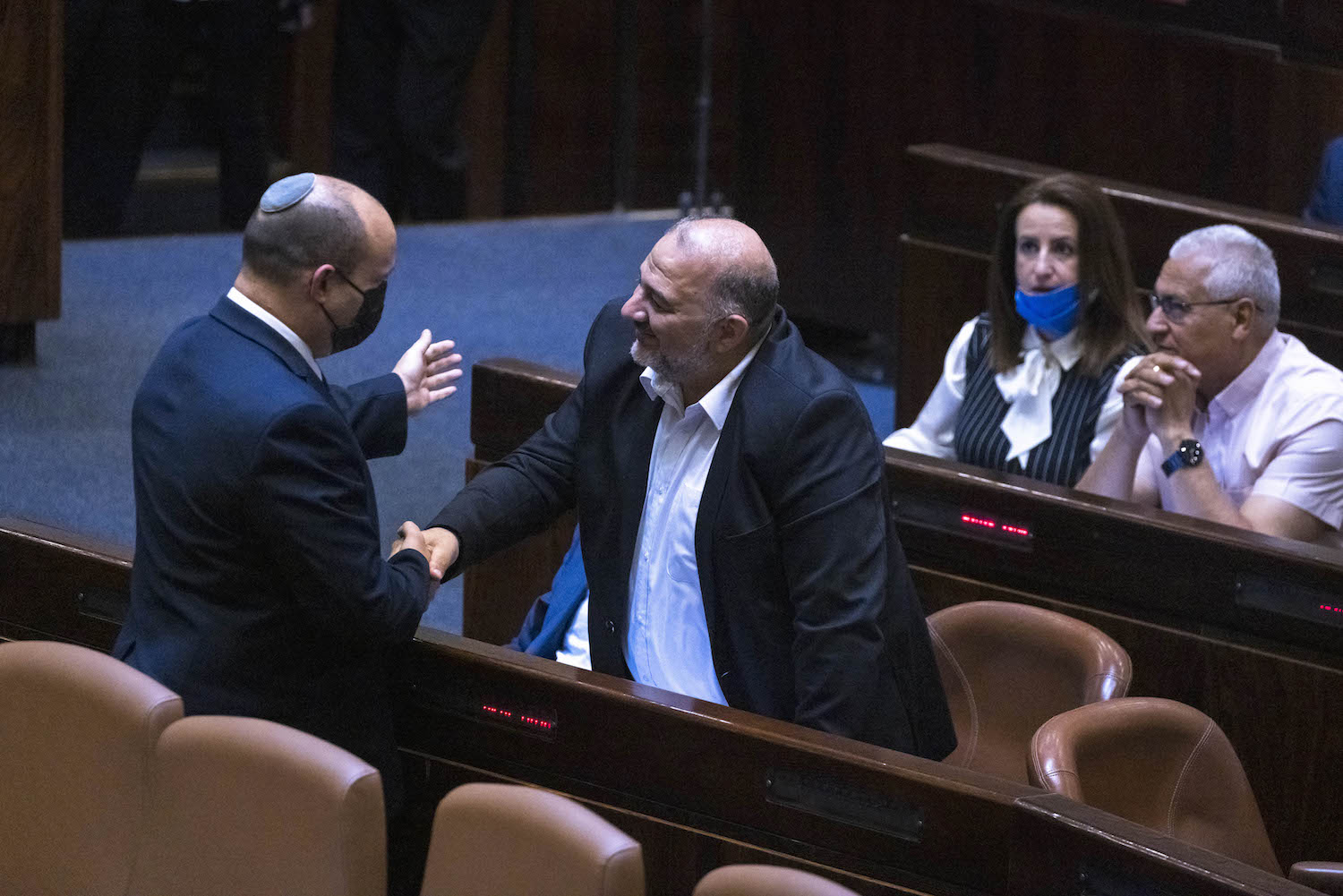 Prime Minister Naftali Bennet shakes hands with head of the Ra'am party, Mansour Abbas, during a plenary session at the assembly of the Knesset, June 28, 2021. (Olivier Fitoussi/Flash90)