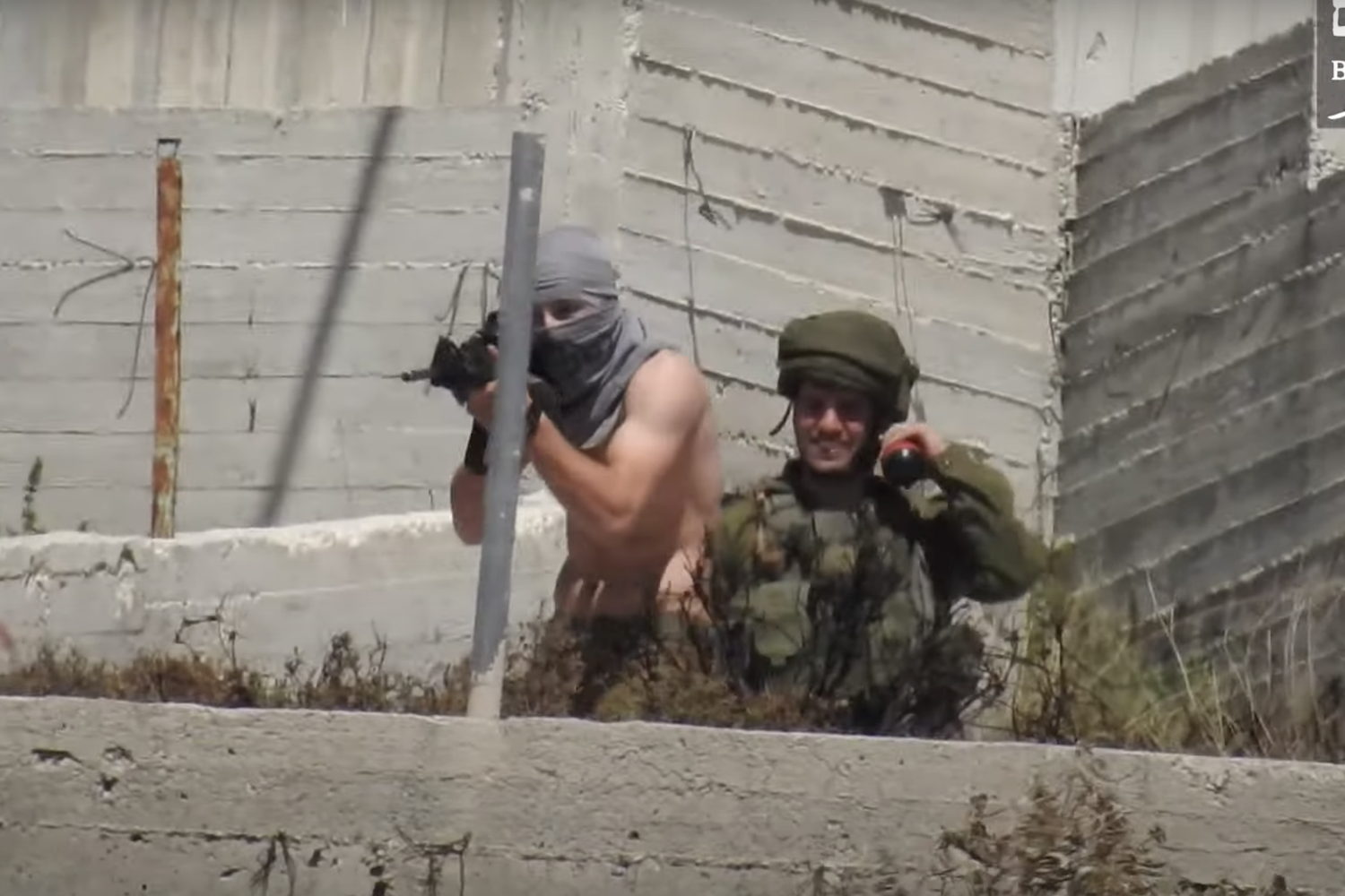 A settler, armed with an automatic rifle, stands directly in front of an Israeli solider as he takes aim and opens fire at Palestinian villagers, Urif, May 14, 20201. (Mazen Shehadeh)