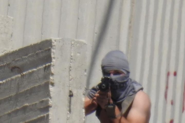 A settler, armed with an automatic rifle, aims and opens fire at Palestinian villagers, Urif, May 14, 20201. (Mazen Shehadeh)