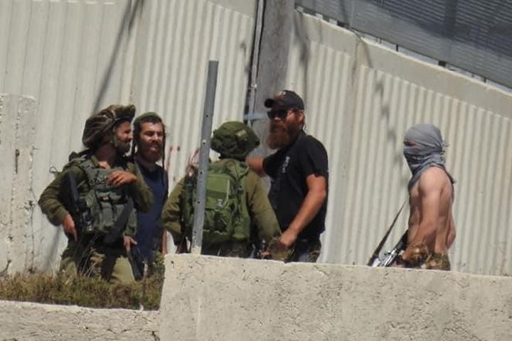 Itzhak Levi, the ongoing security coordinator of the settlement of Yitzhar, seen conversing with soldiers and his other settlers in the Palestinian village of Urif, May 14, 2021. (Mazen Shehadeh)