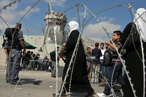 Palestinian women wait to cross Qalandiya checkpoint as an Israeli security officer stands guard outside the West Bank city of Ramallah August 28, 2009. (Issam Rimawi/Flash90)