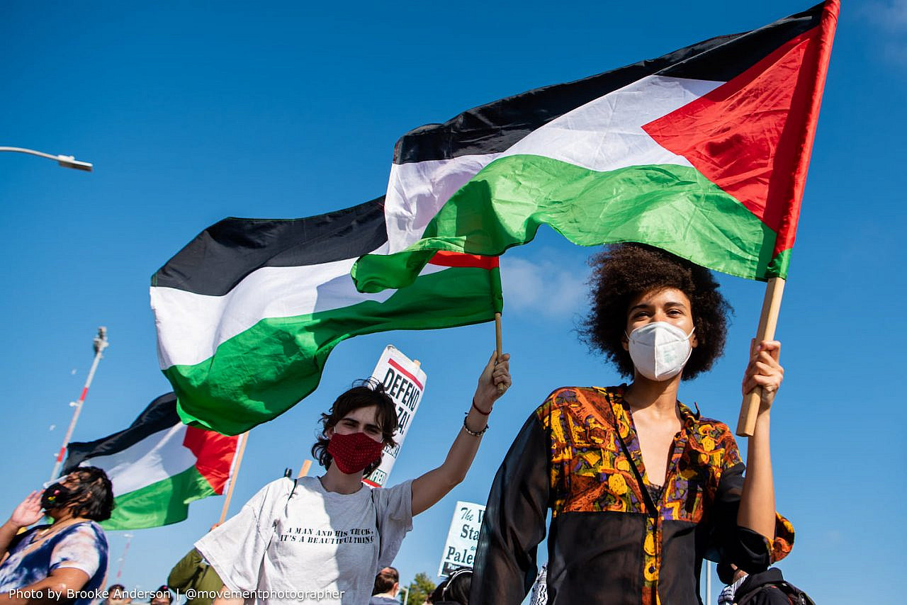 Palestine solidarity activists hoist the Palestinian flag as they move to block an Israeli-owned ship at the Port of Oakland, in protest of Israel's aggressions, June 4, 2021. (Brooke Anderson)