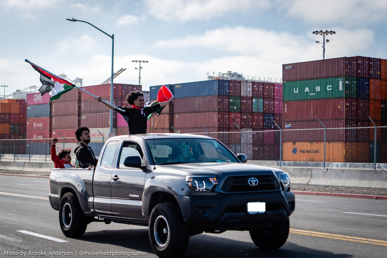 A Palestine solidarity activist hoists the Palestinian flag as demonstrators move to block an Israeli-owned ship at the Port of Oakland, in protest of Israel's aggressions, June 4, 2021. (Brooke Anderson)