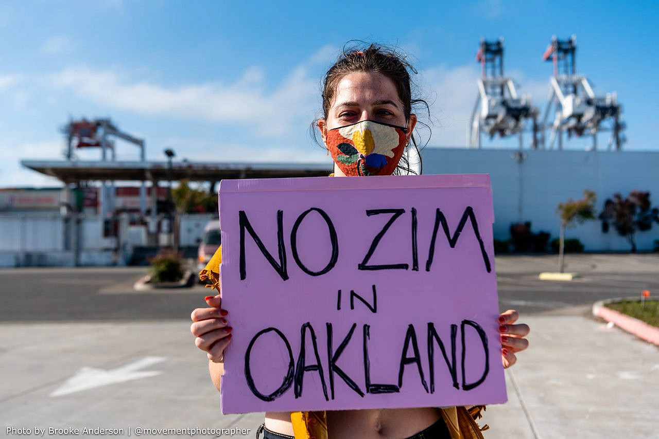 A Palestine solidarity activist holds a sign as demonstrators move to block an Israeli-owned cargo ship from docking and unloading at the Port of Oakland in protest of Israel's aggressions, June 4, 2021. (Brooke Anderson)