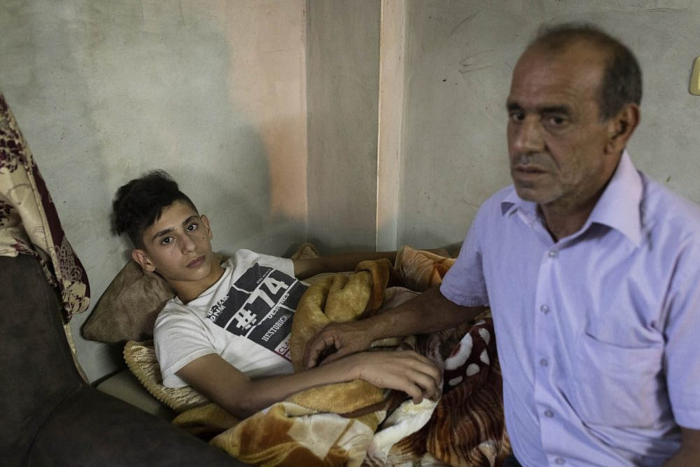 Tareq Zbeideh (left) and his father Abed a-Razeq seen in their family home after Tareq was abducted and brutally attacked by settlers near the former settlement of Homesh, Silat a-Dahr, West Bank. (Oren Ziv)