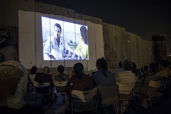 Palestinians watch a film screened on the Israeli Separation Wall as part of a festival, Aida refugee camp, Aug. 29, 2008. (Anne Paq/Activestills)