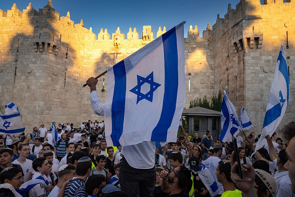 Israelis hold flags and dance during the Flag March at Damascus Gate in Jerusalem's Old City, June 15, 2021. (Olivier Fitoussi/Flash90)