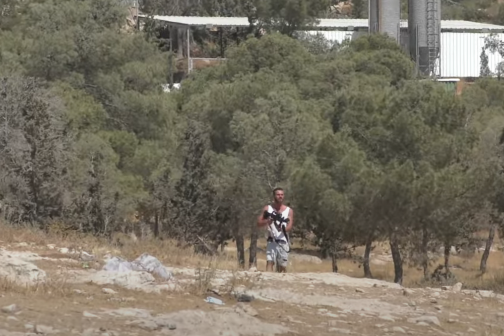 A settler fires at Palestinians from the village of a-Tuwani in the South Hebron Hills using a weapon he had grabbed from an Israeli soldier, June 26, 2021. (Screenshot from video by B'Tselem)
