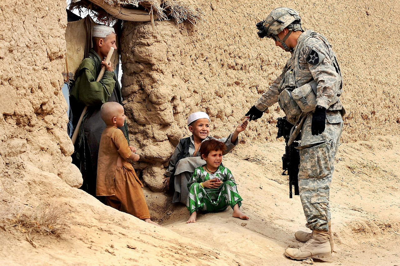 A U.S. soldier gives snacks to Afghan children during a patrol in Dagyan village in Helmand province, Afghanistan, February 21, 2010. (Christine Jones/The U.S. Army)