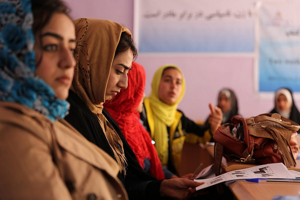 A journalist reviews her training guide during photojournalism training at the Directorate of Women's Affairs building in Farah City, Afghanistan, February 10, 2013. (Josh Ives/U.S. Navy)