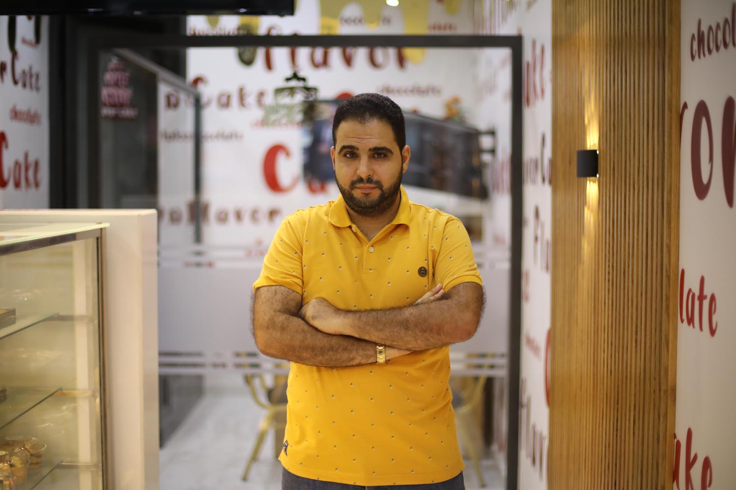 Baraa Rantisi posing at Flavor Cake, the bakery he owns in Gaza City which suffered losses due to the May war on Gaza, September 2, 2021. (Mohammed Zaanoun)