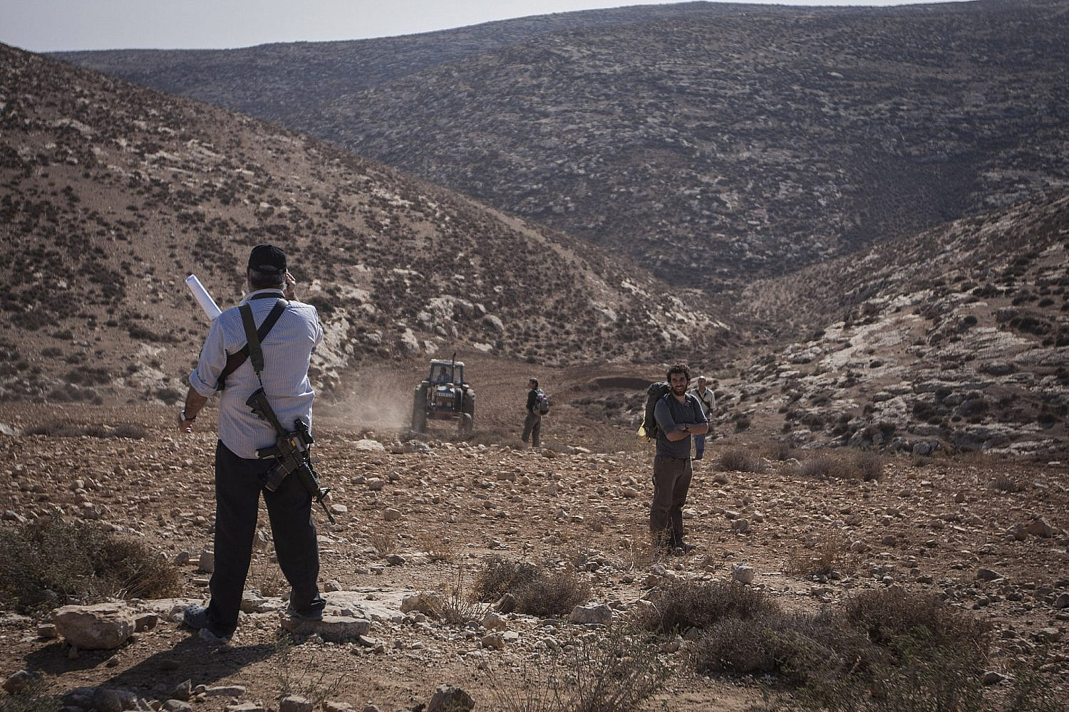 An armed Israeli settler and soldiers during a march and solidarity visit on the Palestinian agricultural lands of Tuba village, South Hebron Hills, West Bank, Dec. 1, 2007. (Shachaf Polakow/Activestills)
