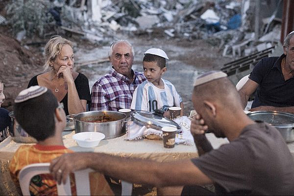 Three families hold an improvised, outdoor Shabbat dinner in the Tel Aviv neighborhood of Givat Amal. Their homes were demolished following a years-long struggle against eviction without proper compensation, September 19, 2014. (Shiraz Grinbaum/Activestills.org)