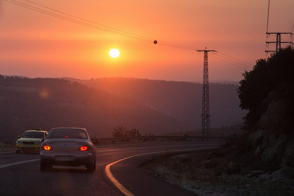 The sun sets over a road in the occupied West Bank. July 22, 2017. (Hadas Parush/Flash90)