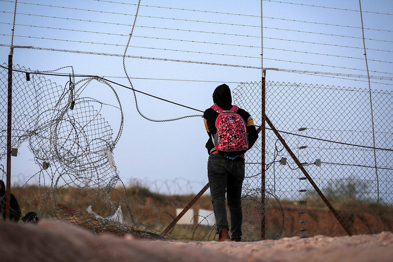 A Palestinian man approaches a hole in the fence near the Mitar checkpoint in the West Bank city of Hebron, on May 5, 2020. (Wisam Hashlamoun/Flash90)