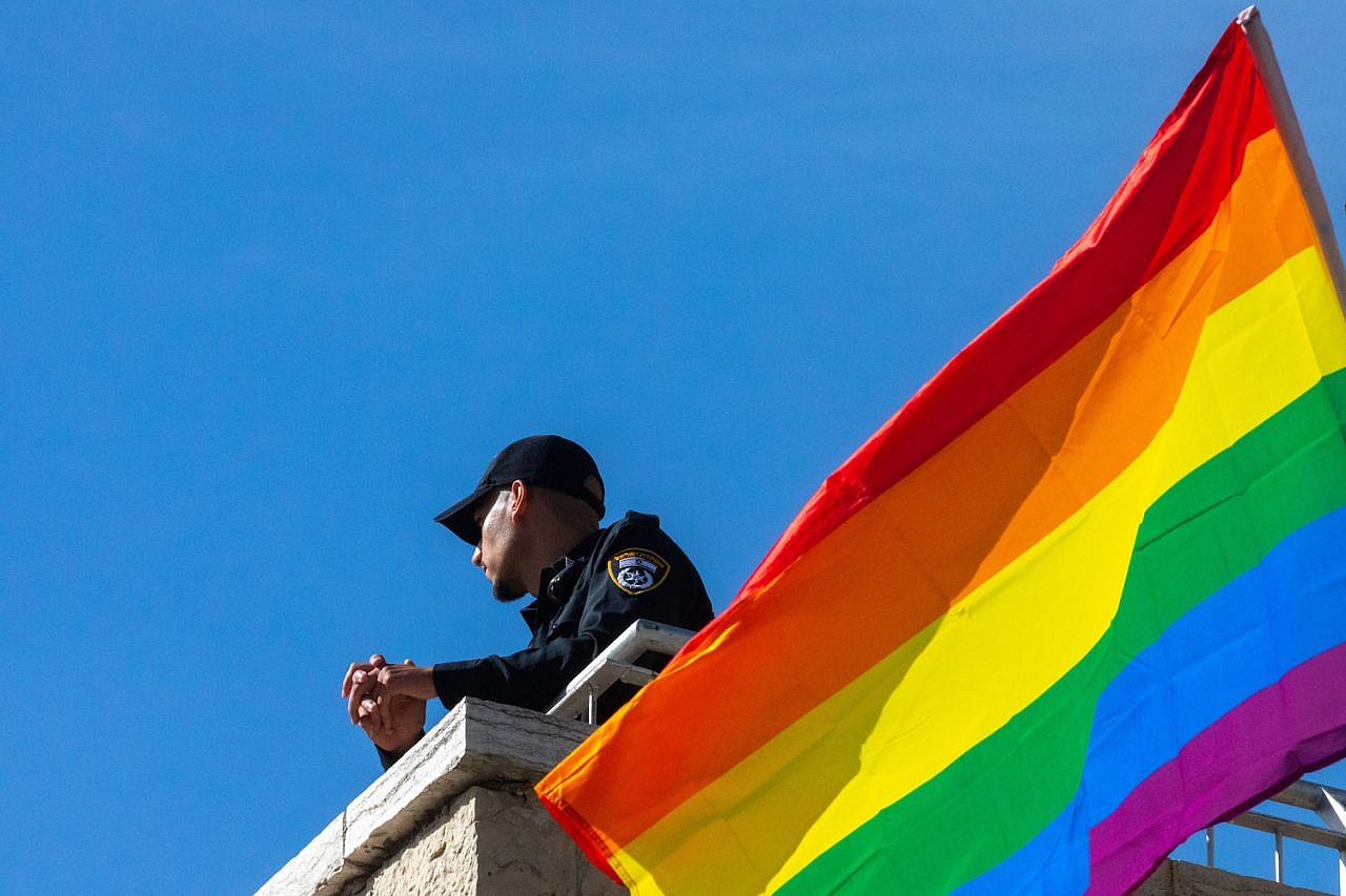 A police officer looks on as people take part in the annual Pride Parade in Jerusalem, June 3, 2021. (Olivier Fitoussi/Flash90)