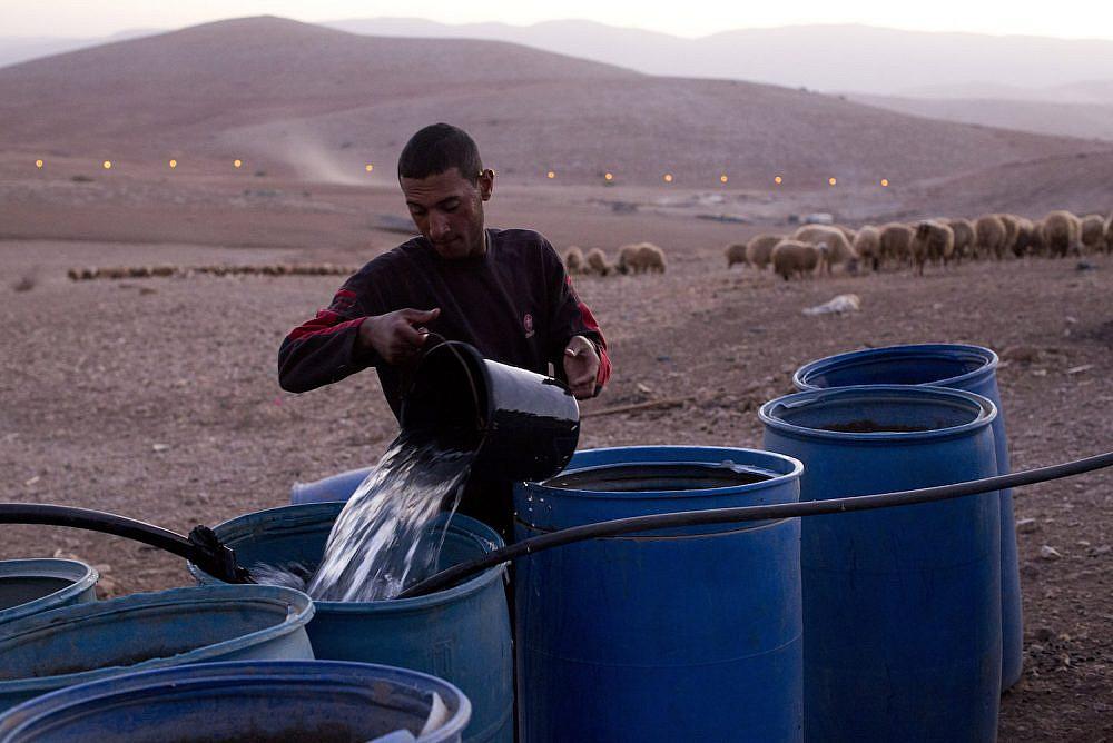 A Palestinian farmer fills water tanks in the West Bank village of Khirbet al-Makhoul, Jordan Valley, October 9, 2013.   (Activestills.org)