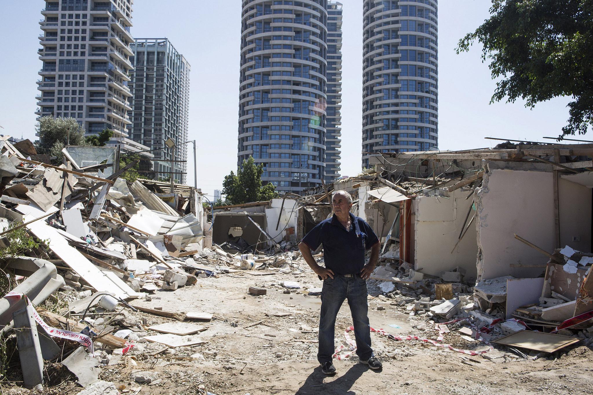 Kaduri Halif stands between the rubble of his destroyed home, Givat Amal, Tel Aviv, September 18, 2014. (Keren Manor/Activestills)