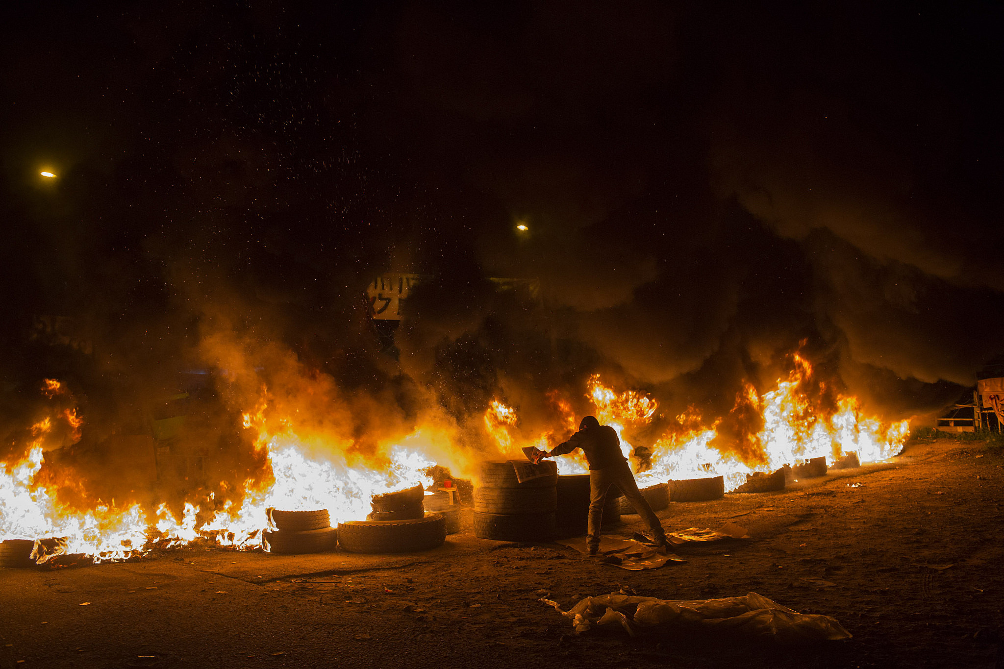 A man sets fire to tires during the eviction of families in Givat Amal, Tel Aviv, December 29, 2014. (Oren Ziv)
