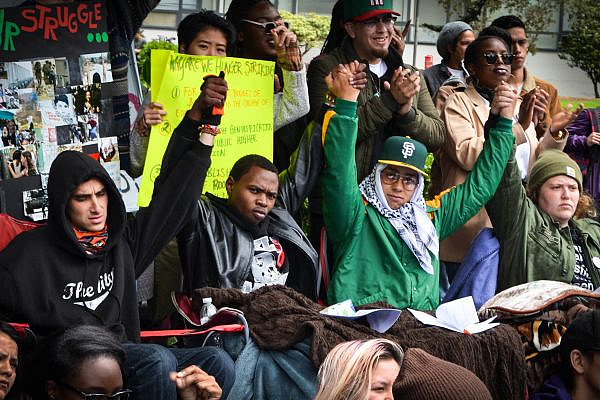 (Center left to right) Sachiel Rosen, Hassani Bell, Ahkeel Mestayer, and Julia Retzlaff, four students referred to as the Third World Liberation Front 2016, who were on a hunger strike to defend the funding of the San Francisco State College of Ethnic Studies, raise their joined hands during an emergency press conference in the Quad, May 9, 2016. (Melissa Minton/CC BY 2.0)