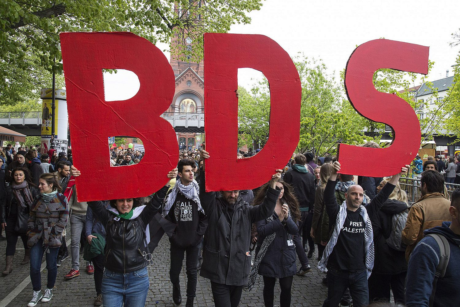 Activists holding a BDS sign march as part of the International Block during the May Day demonstration in Berlin, Germany, May 1, 2017. (Keren Manor/Activestills)