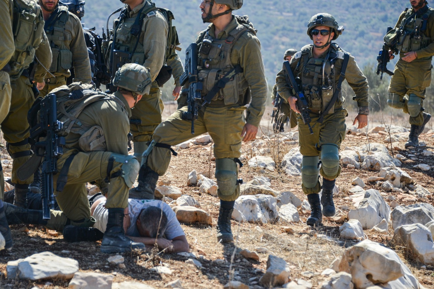 Israeli soldiers hold down and step on prominent Palestinian activist Mohammad Khatib during the olive harvest near a settlement outpost established on Palestinian land in the Salfit area of the West Bank, October 11, 2021. (Matan Golan)