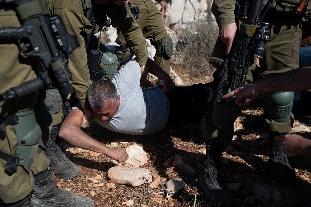 Israeli soldiers hold down prominent Palestinian activist Mohammad Khatib during the olive harvest near a settlement outpost established on Palestinian land in the Salfit area of the West Bank, October 11, 2021. (Matan Golan)
